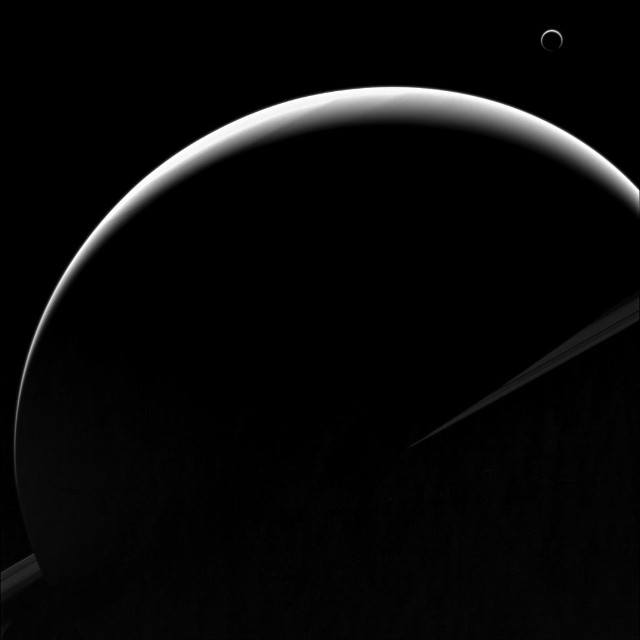 Saturn and Titan are in shadows, showing a crescent phase